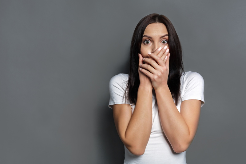 woman-looking-shocked-and-covering-mouth-on-grey-background
