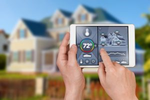 smart-thermostat-in-forefront-with-house-in-background